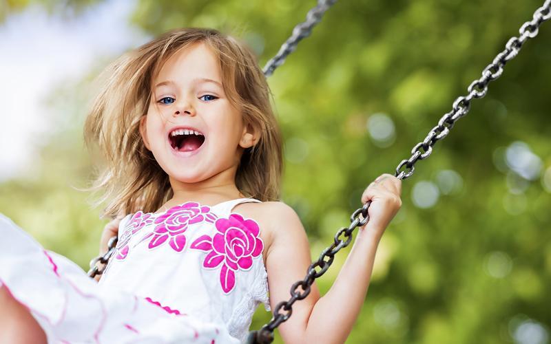 Sweet smiling girl playing on a swing